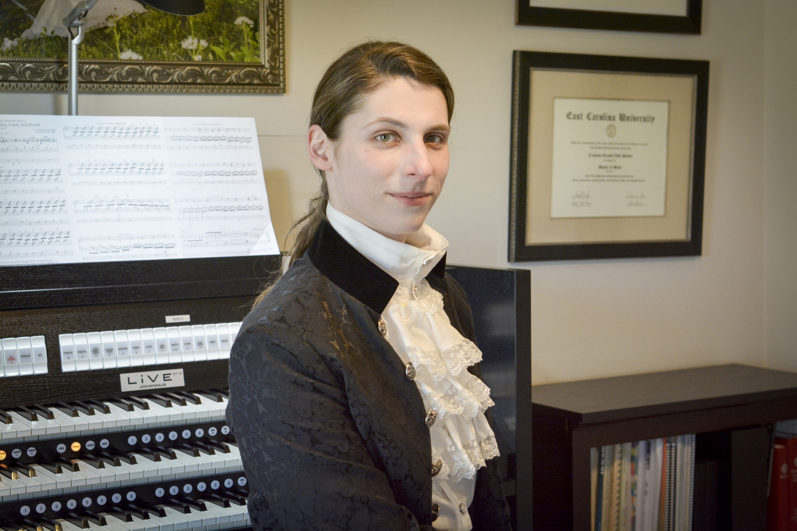 Trans organist and composer Dr. Kris Rizzotto at their home organ (transgender classical musician)