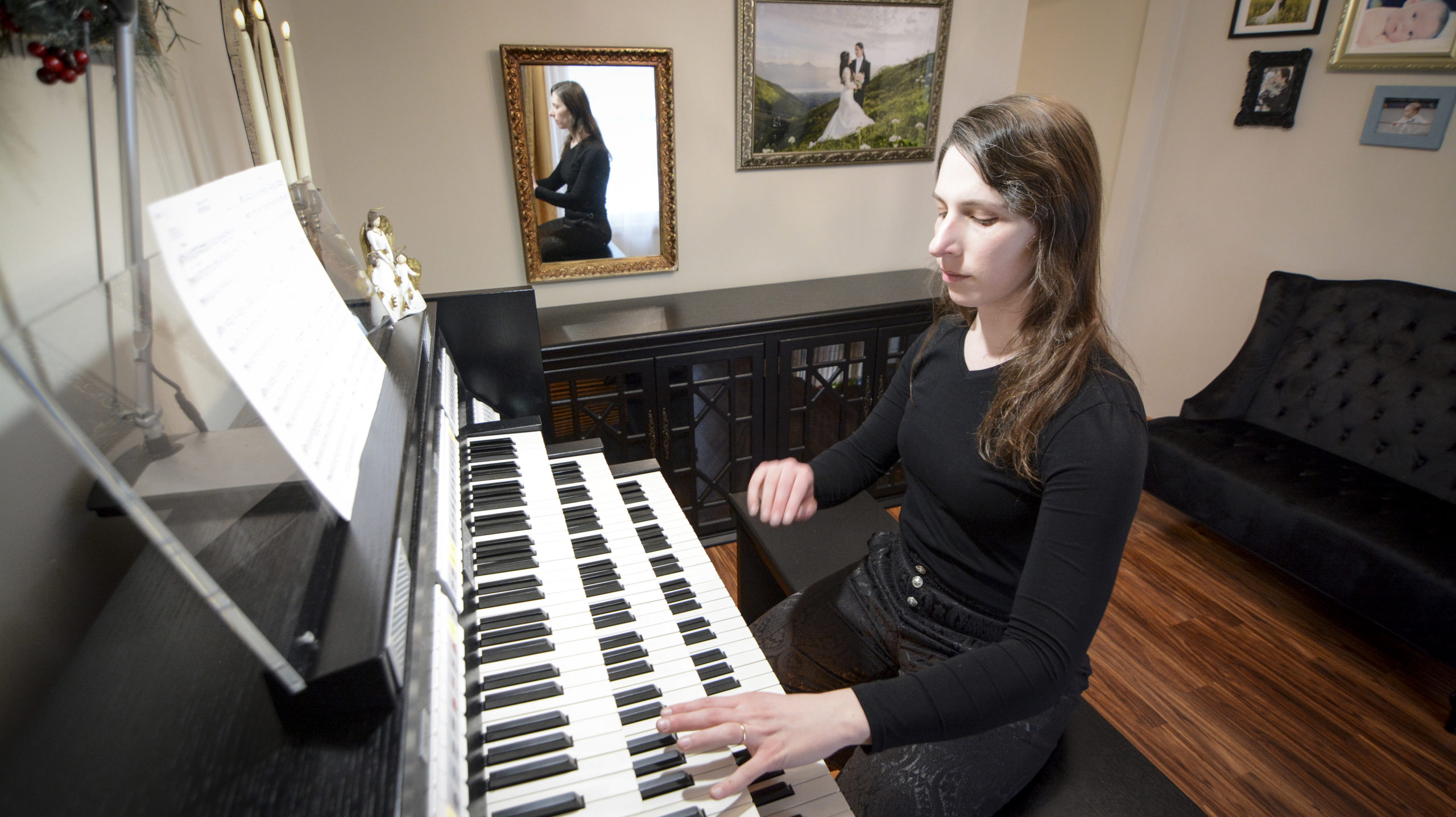 Trans organist and composer Dr. Kris Rizzotto at their home organ, transgender classical musician